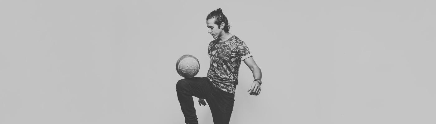 Freestyle voetballer joshua houdt de bal stil op de knie tijdens een fotoshoot voor zijn voetbalschool 4skills soccer academy.