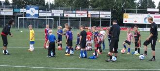 voetbal trainer joshua laat zien op speelse wijze training te geven aan kinderen door middel van een simpele voetbaloefening.
